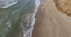 Morning jogging guy along the surf line of the sea beach in summer Stock Footage