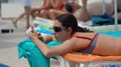Beautiful model is lying by the pool and typing message. - stock footage