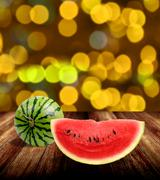Watermelon on wooden tabel with yellow bokeh light background Stock Photos