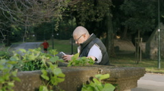 Bold man in a city park using his tablet - stock footage