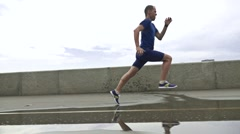 Sportsman running on river embankment after rain and stepping into puddle. Super Stock Footage