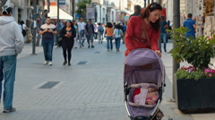 Young woman with baby carriage among a lot of defocused tourists. - stock footage