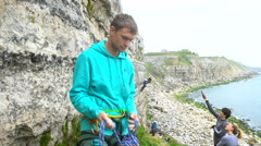 4K Portrait of smiling rock climber standing at base of cliff Stock Footage
