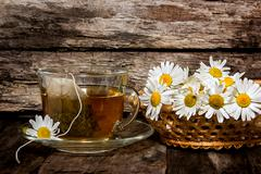 Chamomile tea. Medicinal infusion in a transparent Cup and camomile - stock photo