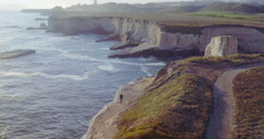 Aerial of Man walking along cliff edge at shark fin cove, santa cruz Stock Footage