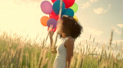 Young girl walking through a wheat field with colour balloons during sunset - stock footage