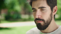 Portrait young attractive man looking serious at the camera in the park Stock Footage