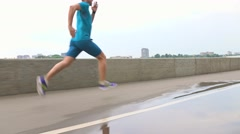 Man in blue uniform running along embankment. Steadicam 4K video Stock Footage