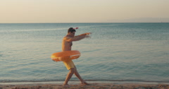 Funny man dancing on the beach - stock footage