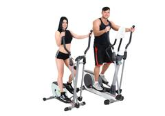 young woman and man doing exercises on elliptical cross trainer - stock photo