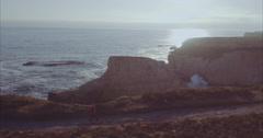 Aerial of Man walking along cliff edge at shark fin cove, santa cruz - stock footage