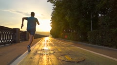 Man in blue uniform running on summer sunset embankment along bicycle road Stock Footage