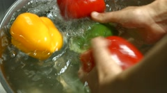 Men's hands washing bell pepper - stock footage