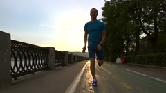 Runner in blue clothes running at the camera along summer sunset embankment of - stock footage