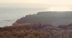 Aerial of Man walking along cliff edge at shark fin cove, santa cruz Stock Footage