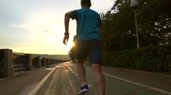 Runner in blue clothes running from the camera along summer sunset embankment of Stock Footage