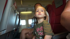 Funny kid and mother in the airplane, ready for take off. - stock footage