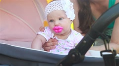 Baby sitting in a stroller with a funny nipple in the form of huge lips - stock footage