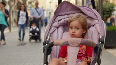 Cute child is in the baby carriage among crowd of tourists. - stock footage