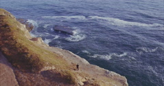 Aerial of  Man sitting on cliff edgde looking out at ocean at shark fin cove, Stock Footage