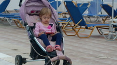Cute baby seats in baby carriage by the pool. Stock Footage