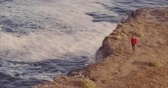 Aerial of Man looking out over ocean cliffs and ocean at Shark Fin Cove, Santa Stock Footage