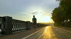 Sportsman in blue clothes running on summer sunset embankment in Moscow. Super Stock Footage