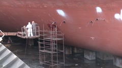 Worker painting ship in the shipyard dry dock Stock Footage