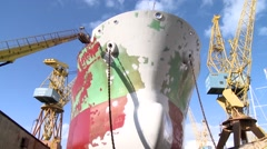 Worker painting ship in the shipyard dry dock timelipse Stock Footage