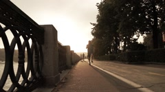 Man running on summer sunset embankment, Moscow. Bleached warm colors. Super Stock Footage