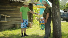 Senior man and father rolls the beautiful baby on a swing. Grandfather with his Stock Footage