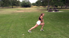 Caucasian teen girl stretching in white shorts black top at park Stock Footage