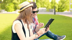 In love couple relaxing in the park using tablet pc - stock footage