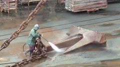 Workers washing rusty anchor chain from ship in dry dock harbor Stock Footage
