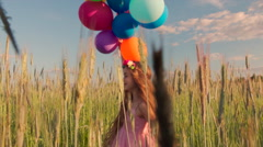 Young girl spinning around in wheat field with colour balloons during sunset Stock Footage