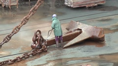 workers washing rusty anchor chain from ship in dry dock harbor - stock footage
