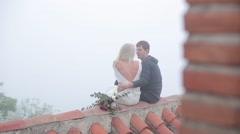 Couple sitting on the roof with red slate - stock footage