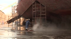 Workers washing ship in dry dock shipyard Stock Footage