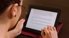 Young beautiful business woman sitting at a table and reading on tablet pc Stock Footage