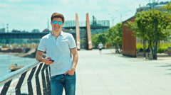 Beautiful student male in sunglasses standing on pier against river and smiling Stock Footage