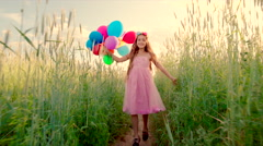 Young girl running through a wheat field with colour balloons during sunset Stock Footage