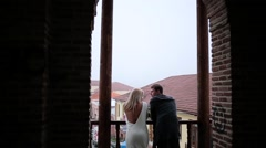 Couple staying on the balkony with old town view Stock Footage