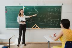 Teacher or docent or educator giving while lesson in front of a blackboard or - stock photo