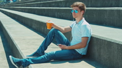 Beautiful student male in sunglasses drinking tea sitting on outdoor in urban Stock Footage