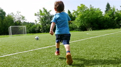 Tracking camera of a little boy scoring a goal in football field - stock footage
