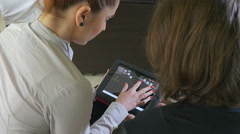 Two business women presenting on a tablet pc - stock footage