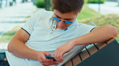 Beautiful student male in sunglasses using cell phone with headphones - stock footage
