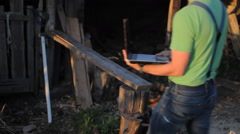 Young man making video call at the sawmill with laptop computer in his hands Stock Footage