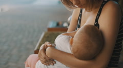 Woman breastfeeds her baby in the Park Stock Footage