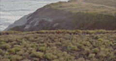 Aerial of Man running along cliff edge at shark fin cove, santa cruz - stock footage